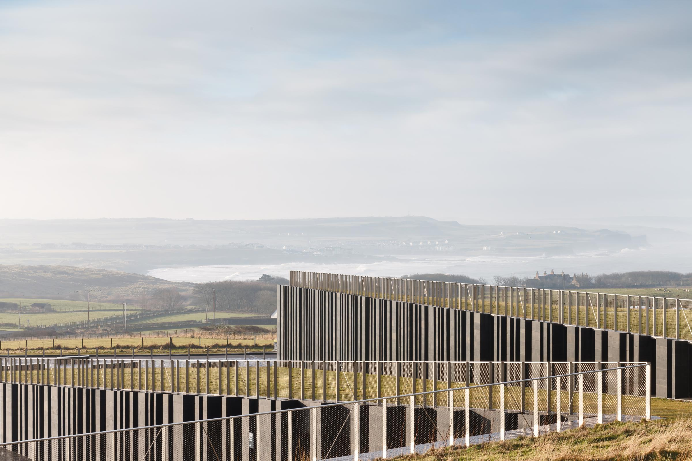 Photograph of Giants Causway Visitor Centre, designed by Heneghan Peng Architects and located in Bushmills, United Kingdom